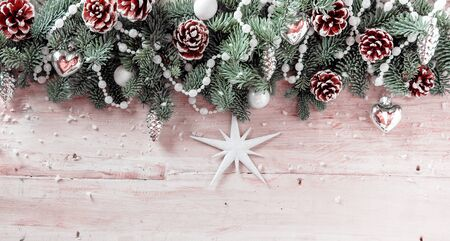 x mass: Panoramic Christmas background with pine cones and green foliage decorated with a garland of beads and Xmas decorations with a star on rustic wooden boards, copyspace for your seasonal greeting Stock Photo