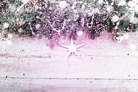x mass: Pink toned snowy Christmas background with a still life arrangement of pine cones and pine foliage decorated with garlands of beads and a star, falling snowflakes and copyspace on rustic wooden boards