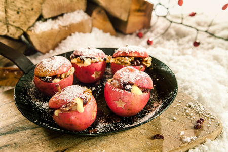 baked: Christmas baked stuffed fresh red apples with a star decoration and raisin and walnut stuffing sprinkled with sugar on a pan outdoors on a rustic wooden board in winter snow