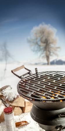 broil: Empty BBQ grill with hot coals standing outdoors in a snowy winter landscape with condiments and spices ready for a winter barbecue party