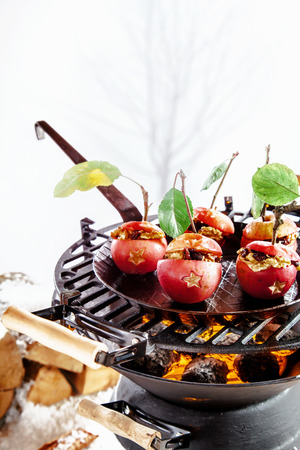 Delicious red stuffed apples with nuts and raisins cooking on the grill of the barbecue outdoors in winter with copyspace for your Christmas greeting