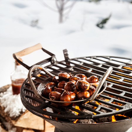 Dish of roasted chestnuts on a barbecue grilling over the hot coals outdoors in a snowy winter landscape ready for a winter BBQ party