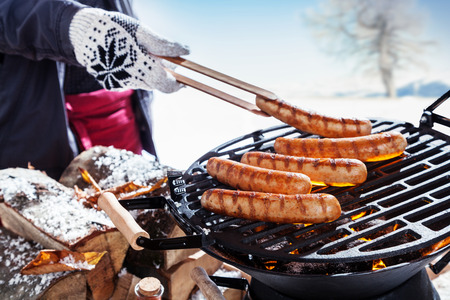 frankfurter: Outdoors winter barbecue party with a person wearing knitted woollen gloves cooking sausages over hot coals in a BBQ, close up view