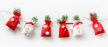 sachets: Advent calendar stuffed sachets in a row hanging on a rope isolate on white background for christmas season