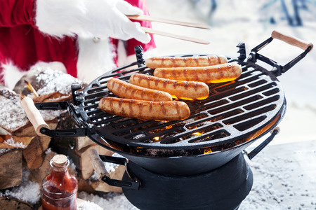 party outfit: Man in Santa outfit grilling sausages outdoors in the snow on a portable barbecue, close up of his hand in a Christmas party concept