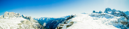 panorama: Snowy winter mountain panorama in a scenic landscape view of rugged rocky peaks under a blue sky in a seasonal, nature and weather concept