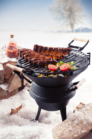 spare ribs: Marinated spare ribs and colorful vegetables cooking on a winter barbecue outdoors in a snowy landscape