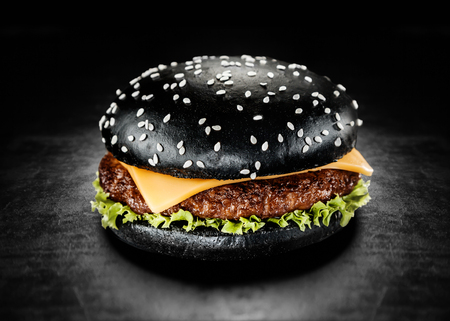 colorant: Japanese Black Burger with Cheese. Cheeseburger from Japan with black bun on dark background