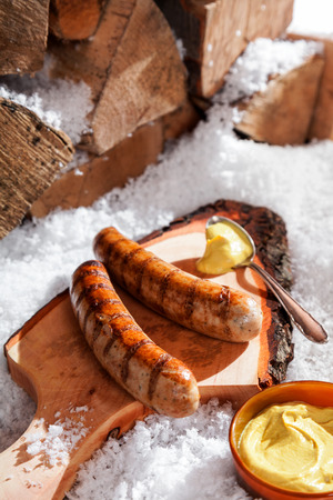 pork: Grilled sausages served on a rustic wooden board with a scoop of mustard outdoors in the snow at a winter grill party