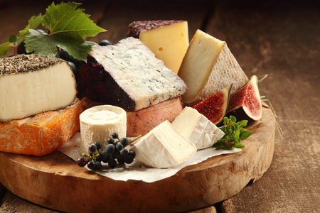 Delicious gourmet cheese platter with a wide assortment of soft and semi-hard cheeses served with sliced sweet fresh figs and grapes on a rustic wooden table with background shadow