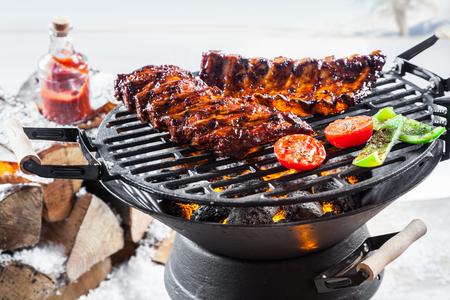 Pittige gemarineerde spare ribs grillen buiten op een draagbare barbecue staande in een besneeuwd winterlandschap tijdens een seizoengebonden, feestelijk grillpartij