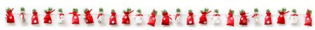 Advent calendar with twenty four red and white bags decorated with sprigs of pine on a white background to be opened one a day through December leading up to Christmas