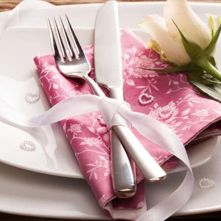 关闭婚礼餐点设置 - 银刀和叉子与白色丝带结束在缎桃红色餐巾和白色板材顶部,装饰着白色玫瑰和微小的珍珠心脏