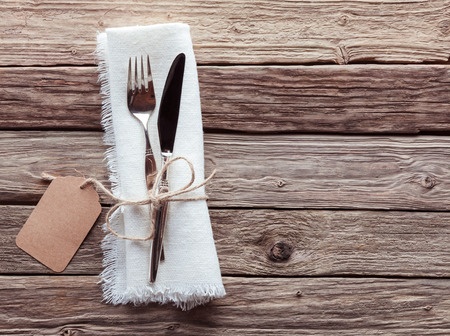 High Angle View of Silver Knife and Fork Tied with String and Blank Tag on White Napkin with Fringed Edges on Rustic Wooden Table with Copy Space