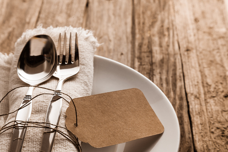 fork and knife: Rustic Christmas place setting with a knife and for on a beige napkin with a blank brown gift tag arranged on a side plate on a wooden table, close up high angle