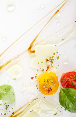 squirted: Abstract artistic background for Italian or Mediterranean cuisine with swirled soy sauce, virgin olive oil, fresh cherry tomatoes, ground spices and fresh green basil leaves over white