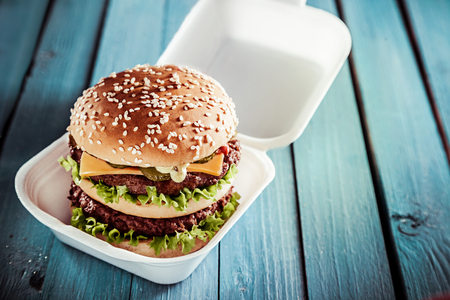 hamburger: Huge double American cheeseburger with juicy beef patties on a sesame bun served in a disposable container as a delicious lunchtime snack on a rustic green table outdoors