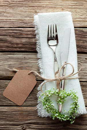 High Angle Close Up of Silver Wedding Knife and Fork Tied with String and Blank Tag on White Napkin with Fringed Edges and Heart Shaped Wreath Made from Greenery and Small White Flowers