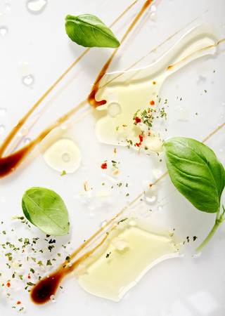 squirted: Artistic abstract background of food ingredients for Italian cuisine with swirled soy sauce, olive oil, ground spice and fresh green basil leaves on a white background