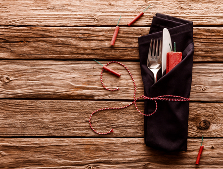 fire crackers: High Angle View of Knife and Fork Wrapped in Dark Colored Napkin and Tied with Striped String on Rustic Wooden Table Surface with Copy Space and Scattered with Fire Crackers
