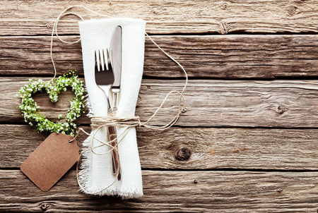High Angle View of Small Heart Shaped Greenery Wedding Wreath at Table Setting with Silver Knife and Fork Tied with String to Fringed White Napkin with Blank Tag on Rustic Wooden Table Surface Stockfoto