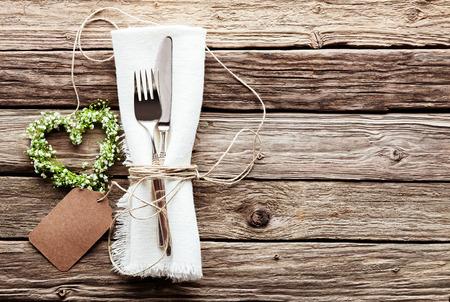 esküvő: Magas, szög, kilátás, kicsi szív alakú zöld esküvői koszorút táblázatot, amely ezüst késsel és villával kötött zsinórral a rojtos fehér szalvéta Blank Tag rusztikus fából készült asztal Surface