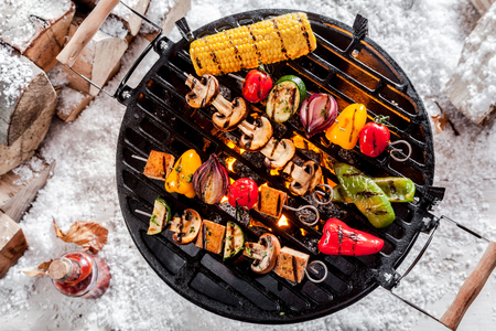 top angle view: Overhead view of colorful vegetable kebabs and a corncob grilling on a winter BBQ outdoors in snow with tasty spicy dips and the wood pile alongside