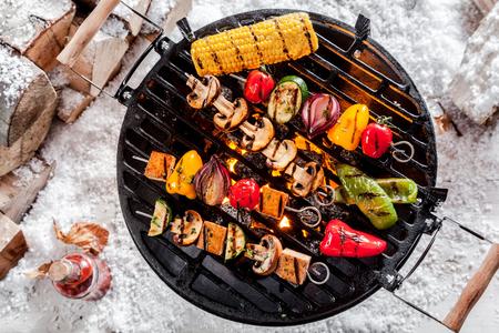 december: Vista de arriba de kebabs vegetales coloridos y una mazorca de ma�z a la parrilla en una barbacoa al aire libre en invierno la nieve con salsas picantes y sabrosas de la pila de madera junto Foto de archivo
