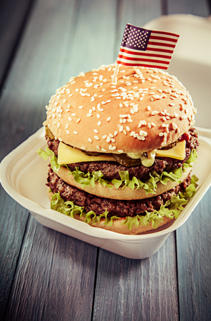 decker: Big double-decker American cheeseburger with crispy lettuce and trimmings on a sesame bun served in a takeaway box with an American flag