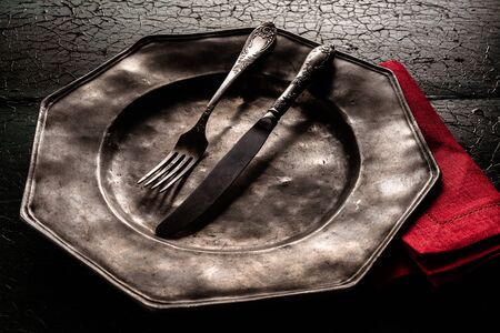 eating utensils: Old rustic vintage octagonal pewter plate with eating utensils and a bright red napkin on a dark textured cracked wood background, close up high angle view