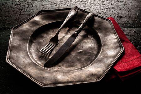 octogonal: placa de la vendimia rústica vieja octogonal estaño con utensilios para comer y una servilleta de color rojo brillante sobre un fondo con textura de madera agrietada oscura, cerca vista de ángulo alto Foto de archivo