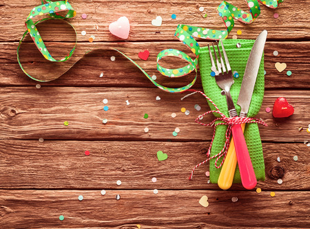 cutleries: Festive party place setting with a colorful bright green napkin with red and yellow cutlery on rustic wooden boards scattered with confetti and hearts and a matching twirled green streamer, copyspace Stock Photo