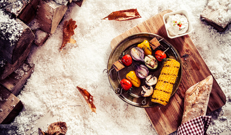 fare: Tasty vegetarian or vegan winter fare with grilled veggie kebabs and corn on the cob on a vintage pewter plate served outdoors in the snow with bread and a savory dip, overhead view