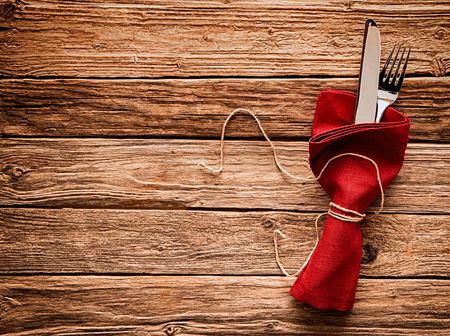 tied in: Colorful rustic festive place setting with a knife and fork tied in a vivid red festive Christmas napkin with string resting on a wooden table with copyspace Stock Photo