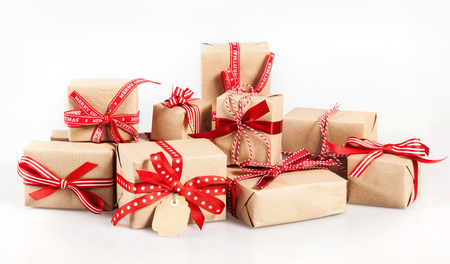 Large stack of decorative Christmas gifts wrapped in brown paper and tied with red ribbon and a bow to celebrate the festive holiday season, over white Foto de archivo