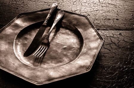 pewter: Old battered rustic pewter plate with cutlery in atmospheric shadowed light on on old cracked textured wooden surface, close up high angle view Stock Photo