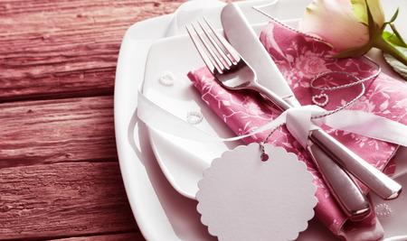 在桃红色餐巾的银刀和叉子附近栓的空白的标记在白色盘子上装饰与白色玫瑰和小珍珠心脏 - 浪漫婚礼餐位设置与拷贝空间