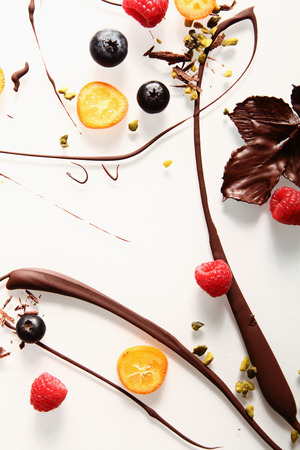 Abstract artistic chocolate swirl background with colorful candied kumquat, raspberries, blueberries pistachio nuts and chocolate coated leaves on white