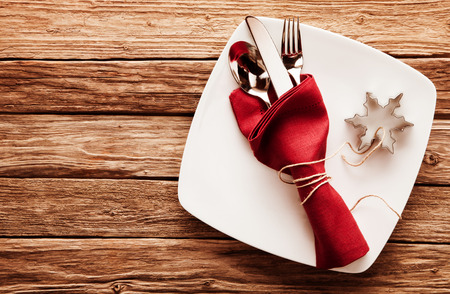 christamas: High Angle View of Silver Cutlery Set Wrapped in Red Linen Napkin and Snowflake Shaped Cookie Cutter on Stylish Square White Plate with Rustic Wooden Background with Copy Space