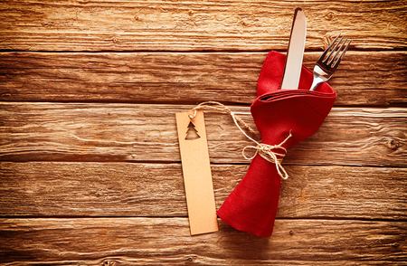 christamas: Rustic colorful red Christmas place setting with cutlery wrapped in a red napkin with a gift tag decorated with an Xmas tree on a wooden table with copyspace
