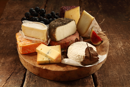 Assorted gourmet cheeses on a rustic wooden platter with soft, semi-hard, goat milk and speciality varieties served with fresh figs and grapes Stock Photo