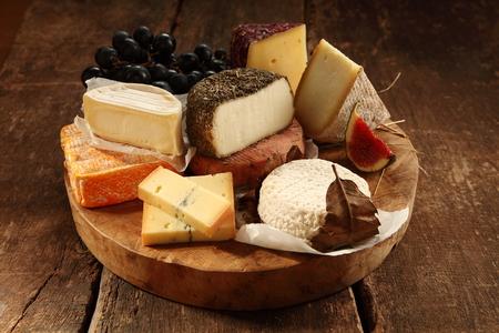 leche y derivados: Surtido de quesos gourmet en un plato de madera rústica con blando, semiduro, leche de cabra y de la especialidad variedades servido con higos frescos y uvas