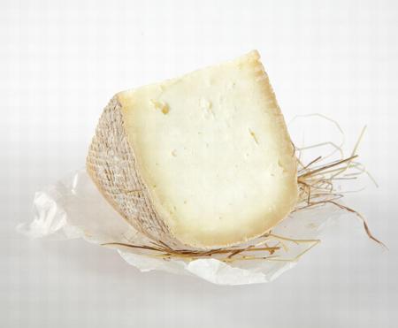 queso blanco: Cuña de Queso semi-curado Cortar en redondo en trozo de papel de cera con la paja en el fondo blanco