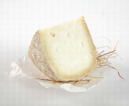 white cheese: Wedge of Semi-Soft Cheese Cut from Round on Piece of Wax Paper with Straw on White Background