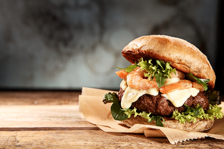 Tasty grilled prawn and beef burger with lettuce and mayonnaise served on pieces of brown paper on a rustic wooden table of counter, with copyspace Stockfoto