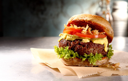 trimmings: Tasty rustic burger with a juicy meat patty, salad trimmings and mayo served on brown paper on a wooden counter, side view with copyspace Stock Photo