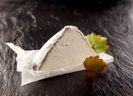 garnish: Still Life - Wedge of Gourmet Cheese with Green Leaf Garnish on Piece of Wax Paper with Dark Rough Textured Surface Background Stock Photo