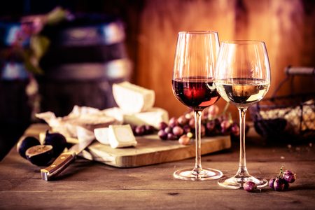 Käseplatte mit frischen Trauben und Gläser Rot- und Weißwein auf einem rustikalen Holztisch vor einem lodernden Feuer in einer Taverne oder Winzer