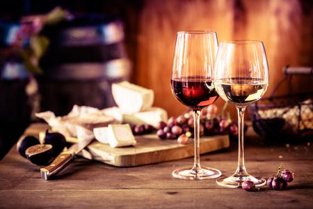 queso: Tabla de quesos con uvas frescas y vasos de vino tinto y blanco sobre una mesa de madera rústica delante de un fuego ardiente en una taberna o bodega