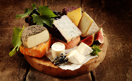 Gourmet cheese platter on a rustic buffet with a large assortment of tasty regional and speciality soft and semi-hard cheeses displayed with fresh grapes and figs, close up view